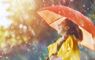 Laughing girl holding an umbrella in the rain